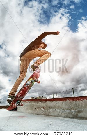A young skateboarder makes Wallie in a skatepark, jumping on a skateboard