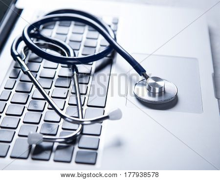 Stethoscope with a modern laptop. Online medicine consulting concept.