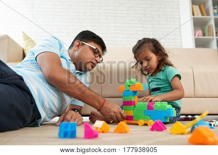 Indian father and daughter sitting on the floor and playing with colorful blocks