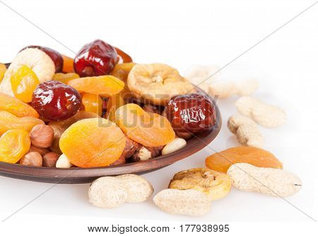 Dried fruits on a white background. Dates lemon apricots figs and nuts in a clay plate.