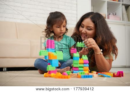 Beautiful Indian woman helping her daughter to build from colorful blocks