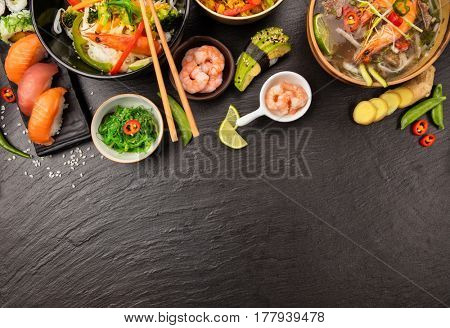 Asian food table with various kind of chinese food, noodles, chicken, prawn soup, rice, sushi and many others. Served on black stone table, top view. copyspace for text