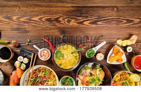 Asian food table with various kind of chinese food, noodles, chicken, pork, beef, rice, spring rolls, sushi, prawns and many others. Served on old wooden table, top view. Copyspace for text