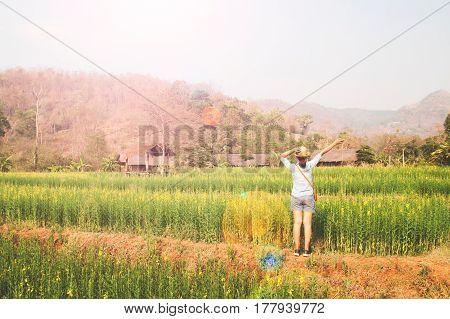 Happy girl traveler standing in flowers field Summer vacation