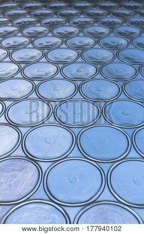 Azure window with circular panes of swirled glass. Shallow depth of field.