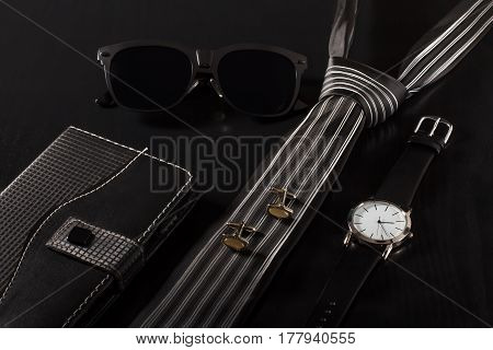 Notebook in leather cover sunglasses tie cuff-links watch with a leather strap on a black background