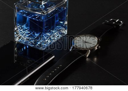 Man perfume watch with a leather strap sell phone on a black background