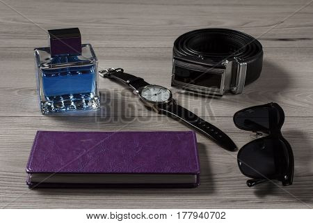 Man perfume watch with a leather strap leather belt with metal buckle notebook in purple cover black sunglasses on a gray wooden background