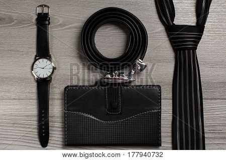Leather belt with metal buckle watch with a leather strap silk tie notebook in leather cover on a gray wooden background