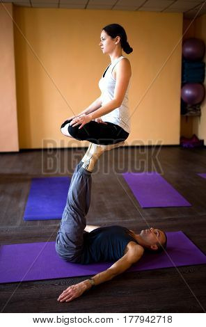 Acro Yoga. Girl Sitting In Padmasana, Lotus Pose On Feet Of Man Indoors