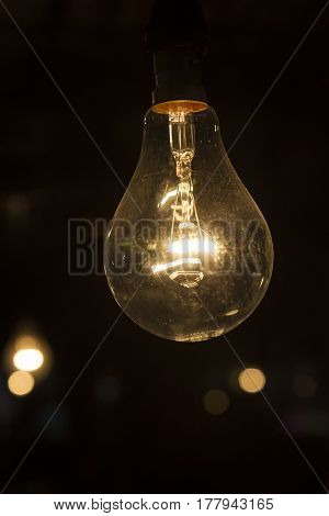 incandescent lamp in dark background with light bokeh