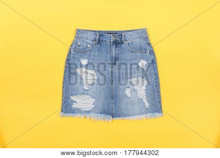 Blue denim skirt isolated on yellow background