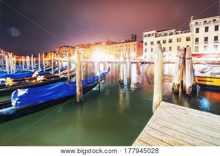 City Landscape. Rialto Bridge Ponte Di Rialto In Venice, Italy At Night. Many Tourists Visiting The