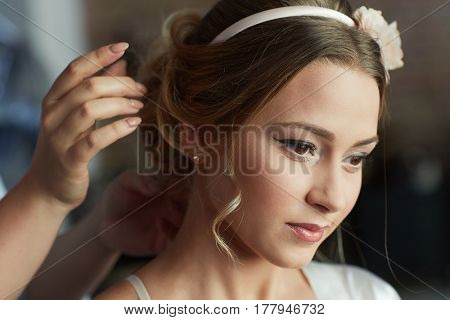 Hairdresser working on bridal knot of hair.