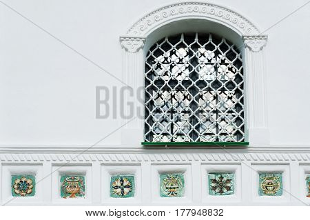 Window with lattice and tiles decoration of Trinity cathedral in Pskov Kremlin