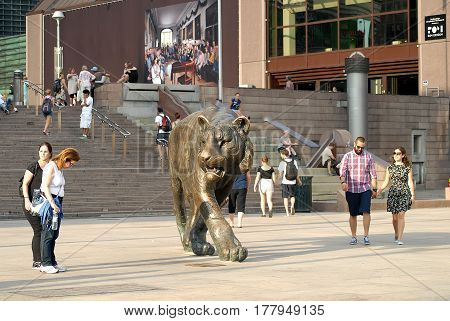 Oslo Norway - July 22 2014: group of people around the sculpture Tiger. In anniversary year 2000 (1000 years to Oslo) large bronze sculpture of tiger made by Elena Engelsen was erected in front of Oslo Central Station