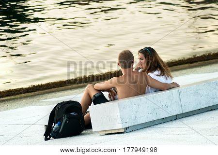 Oslo Norway - July 22 2014: couple sitting on the embankment of Bjorvika bay near Opera house