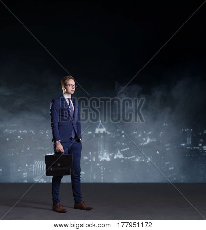 Businessman with briefcase standing on a night city background.  Job, business, career, concept.