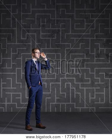 Businessman standing on a labyrinth background. Business, strategy, concept.