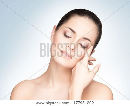 Portrait of young, beautiful and healthy woman: over blue background. Healthcare, spa, makeup and face lifting concept.