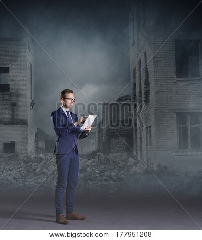 Businessman standing with computer tablet on apocalyptic background. Crisis, default, setback concept.