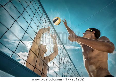 Beach Volleyball players in sunglasses under sunlight. Dynamic sport action near the net, outdoor.
