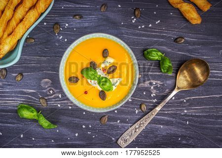 Pumpkin and carrot cream soup with pumpkin seeds and blue cheese on a dark wooden background.Top view