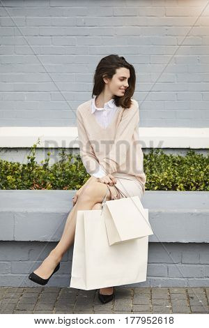 Woman sitting down with shopping bags smiling