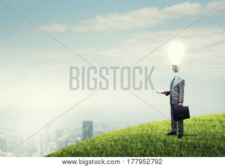 Businessman outdoor with suitcase and bulb instead of head