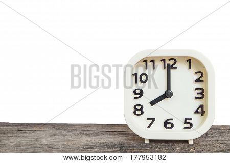 Closeup white clock for decorate in 8 o'clock on old brown wood desk isolated on white background with copy space