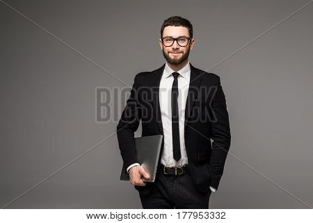 Handsome Business Man In Glasses And Suit Holding Laptop In Hands Side View Isolated Gray Background