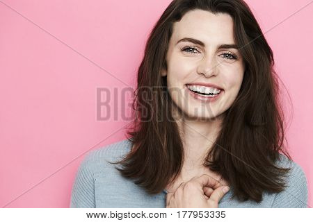 Portrait of beautiful smiling woman against pink background