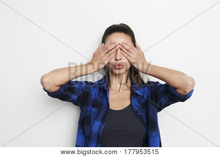 Brunette woman with hands covering eyes studio