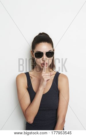 Cool girl with finger on lips studio