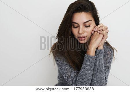Stunning brunette looking down in grey studio