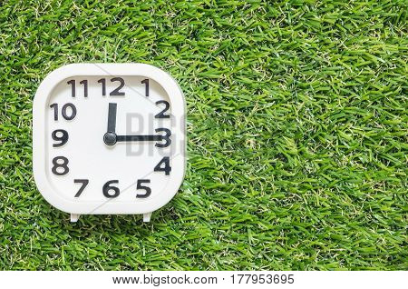 Closeup white clock for decorate show a quarter past twelve o'clock or 12:15 p.m. on green artificial grass floor textured background with copy space