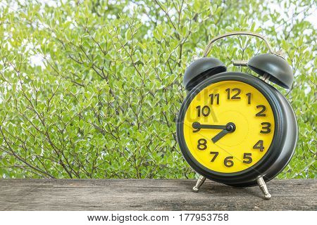 Closeup black and yellow alarm clock for decorate show a quarter to seven o'clock or 7:45 a.m. on old brown wood desk on green leaves in the park textured background