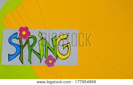 Veer laid sheets of green and yellow paper they have a white sheet painted with the word