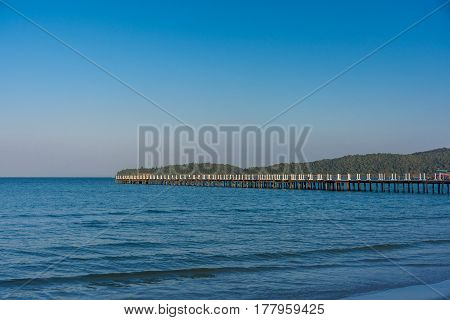A Wooden White Posted Jetty Pier Goes Out In To A Calm Bay With Tree Lined Headland In The Distance.