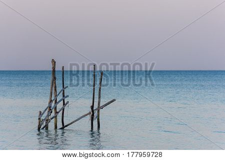 A Frame Made From Old Wooden Posts Stands In A Calm Sea At Golden Hour.