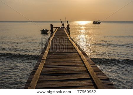 A wonky wooden jetty pier goes out in to a calm sea with small boats around with golden hour lighting.