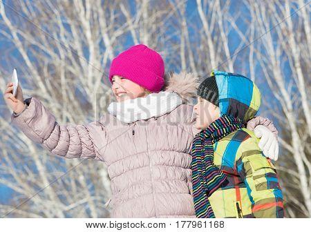 Two happy kids making selfie photo in winter park