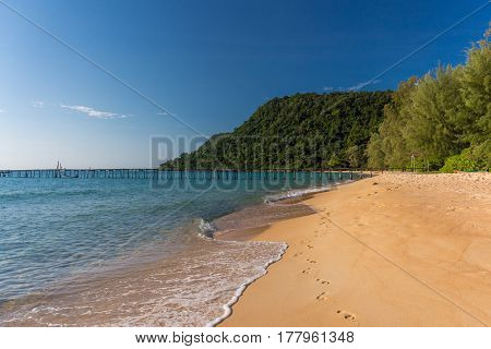 Golden Sandy Beach Of Tropical Island With Forested Headland