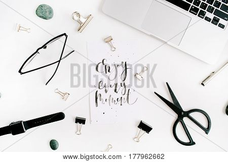 White office desk workspace with quote Enjoy Every Moment and office supplies. Laptop scissors pen clips glasses on white background. Flat lay top view.
