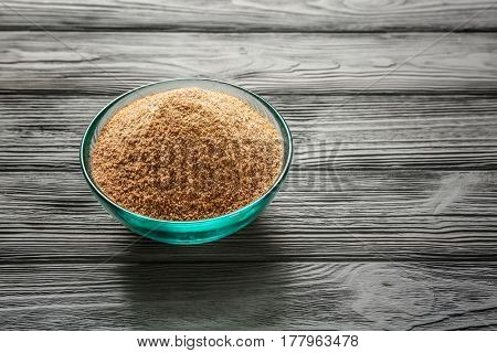 Glass bowl with bread crumbs on wooden table