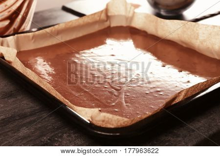 Unbaked cocoa cake in baking dish on table