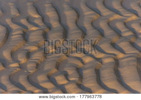 Close up of sandy golden beach at golden hour with ripple pattern left by the tide and waves.