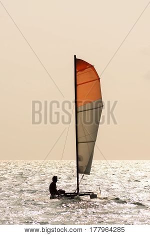 Small twin hull sailing boat with one person on board on calm ocean.