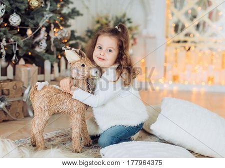Beautiful and happy little girl near Christmas tree