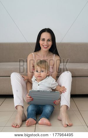Young woman using tablet with her son sitting on floor near couch